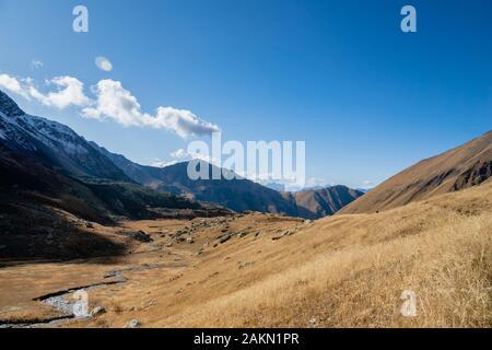 Juta trekking path landscape with river and mountains in sunny autumn day -  popular trekking  in the Caucasus mountains, Kazbegi region, Georgia.