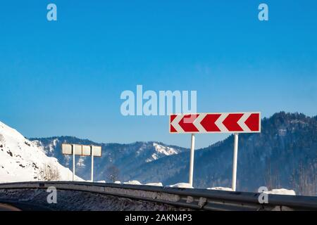 Road sign warning of a sharp and dangerous turn to the left with red arrows on a white background with mountains, snow in winter. - Stock Photo