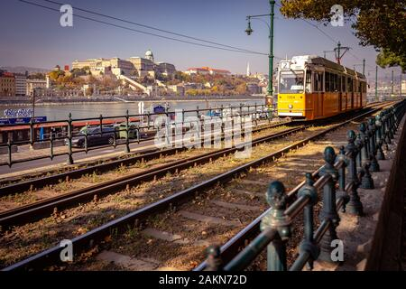 Budapest, Hungary - Local tram riding along the river with Buda castle in the background - Stock Photo