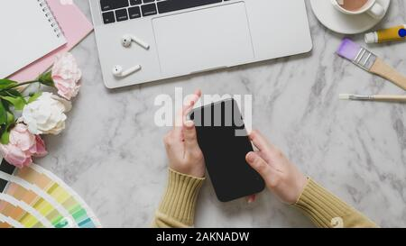 Top view of young female artist holding smartphone in modern workspace with laptop, wireless headphone and painting tools on marble desk background - Stock Photo
