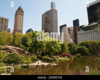A view of the New York City skyline from across a lake in Central Park with blossoming trees reflecting on the water on a spring day. - Stock Photo