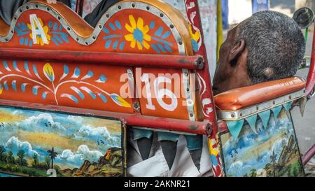 KOLKATA,WEST BENGAL/INDIA-MARCH 19 2018:A cycle rickshaw driver dozes in his colorful cart on the streets of Calcutta. - Stock Photo