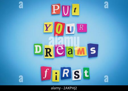 Put your dreams first. Positive thinking concept. Text of cut colorful letters on blue background. Writing on banner, card. Inscription, message on po