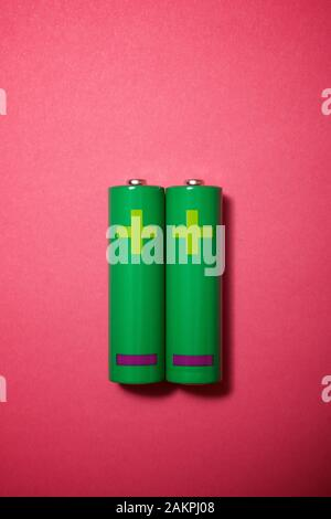 Two small batteries on a pink table. - Stock Photo