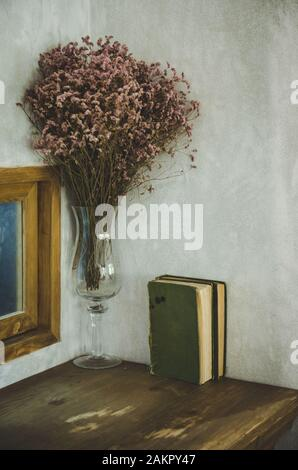 book on table with dry flowers in glass vase