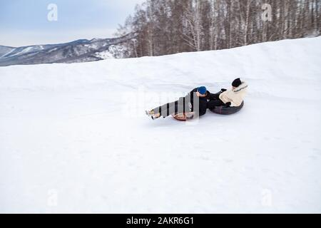 Altai, Russia - 01.01.2020:  A couple of man and woman are having fun and riding from the mountain in the snow on  two an inflatable round snow tube. - Stock Photo