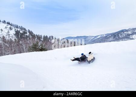 A couple of man and woman are having fun and riding from the mountain in the snow on  two an inflatable round snow tube. Winter sports and family ente - Stock Photo