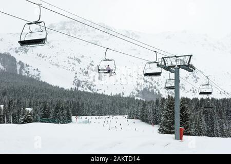 Chairlift with skier at Meribel ski resort, France - Stock Photo