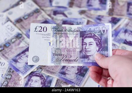 Holding a British English sterling twenty pound note with more notes in the background - Stock Photo