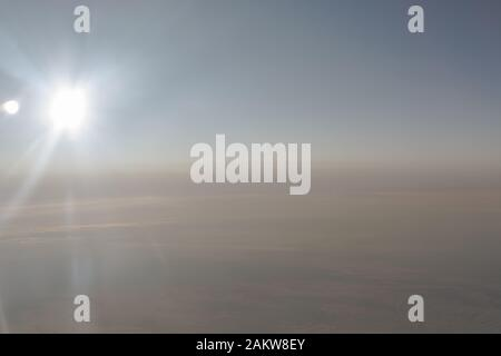 In the air, view of the airplane wing with horizon of dark blue sky and clouds background in sunrise time, viewed from the airplane window - Stock Photo