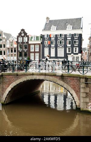 Bridge on Amsterdam Canal with bicycles attached to railings and traditional narrrow houses