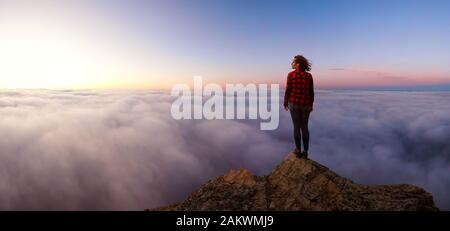 Adventurous Girl on a Rocky Mountain above the Clouds