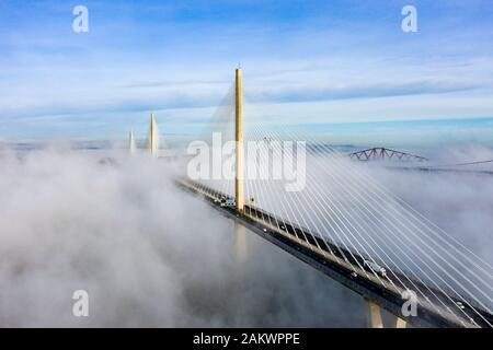 South Queensferry, Scotland, UK. 10th Jan 2020. Drone image of a spectacular cloud inversion at Queensferry Crossing Bridge with the lower half of the bridge shrouded in fog but the upper half in beautiful sunny weather. In background the Forth Bridge and Forth Road Bridge. Iain Masterton/Alamy Live News - Stock Photo