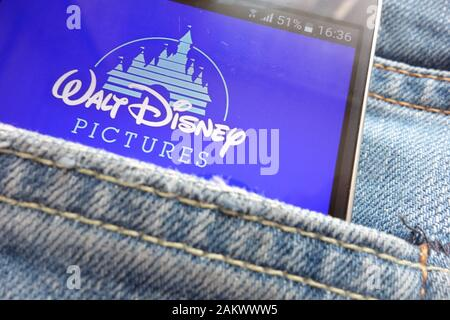 Walt Disney Pictures logo displayed on smartphone hidden in jeans pocket - Stock Photo