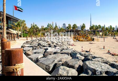 Dubai / UAE - December 20, 2019: La Mer Beach in Dubai. New modern public urban beach with beautiful city background. La Mer walk wuth UAE flag - Stock Photo