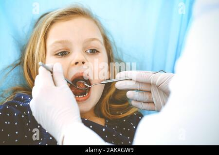 Little baby girl sitting at dental chair with open mouth during oral check up while doctor. Visiting dentist office. Medicine concept. Toned photo - Stock Photo