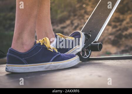 Close up view of teen's feet on a scooter ready to start a ride over the half pipe. Skater starting jumps and tricks at the skate park. Let's go enjoy