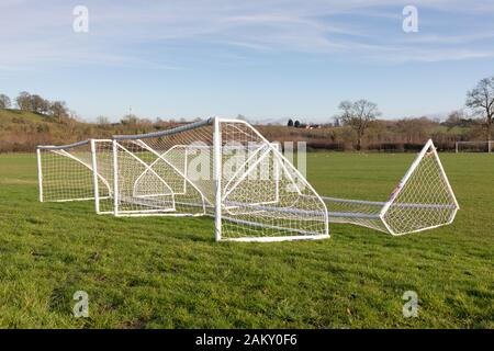 Crick, Northamptonshire, UK: Four white-framed and netted five-a-side football goal mouths laying on the grass of a playing field in a rural location. - Stock Photo