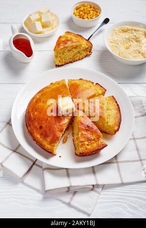 Homemade sliced Buttermilk Cornbread topped with melted butter served on a plate with maple syrup in a gravy boat on a white wooden table, vertical vi - Stock Photo