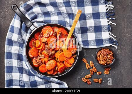 Candied sweet potatoes with brown sugar, maple syrup, orange juice and pecan nuts in a skillet on a concrete table with kitchen towel, view from above - Stock Photo