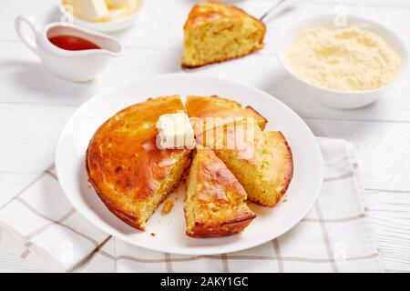 Homemade sliced Buttermilk Cornbread topped with melted butter served on a plate, ingredients and maple syrup at the background, horizontal view from - Stock Photo