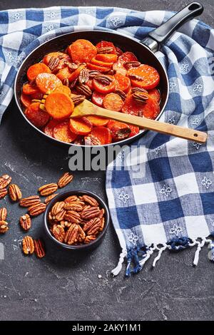 Candied sweet potatoes with brown sugar, maple syrup, orange juice and pecan nuts in a skillet on a concrete table with kitchen towel, vertical view f - Stock Photo