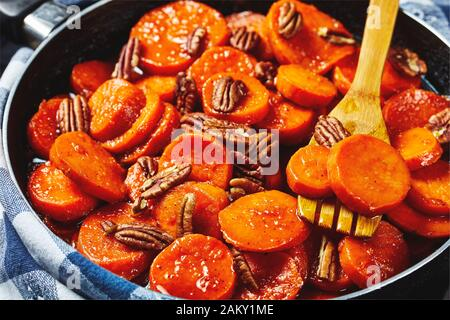 Candied sweet potatoes with brown sugar, maple syrup, orange juice and pecan nuts in a skillet with wooden spatula, view from above, close-up, macro - Stock Photo