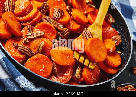 Candied sweet potatoes with brown sugar, maple syrup, orange juice and pecan nuts in a skillet with wooden spatula, horizontal view from above, close- - Stock Photo