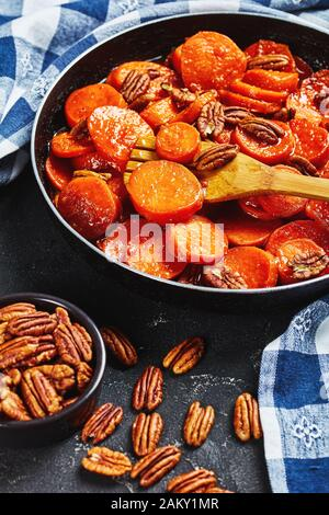 close-up of Candied sweet potatoes with brown sugar, maple syrup, orange juice and pecan nuts in a skillet with wooden spatula, vertical view from abo - Stock Photo