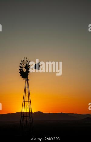 Windmill silhouetted against orange sky, Organ Mountains, near Las Cruces, New Mexico USA - Stock Photo