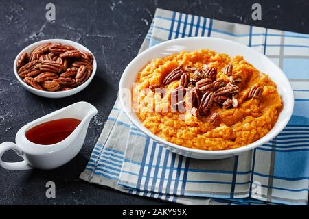 sweet potato mash topped with pecan nuts in a bowl with maple syrup in a white sauceboat on a concrete table, view from above - Stock Photo