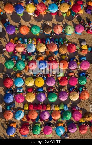 Top down aerial view of colourful beach umbrellas at famous Seminyak Beach in Bali, Indonesia. - Stock Photo