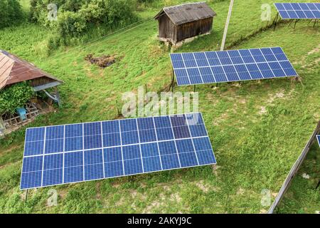 Aerial top down view of solar panels in green rural area. - Stock Photo