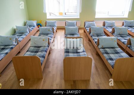 Many small beds with fresh linen in daycare preschool empty bedroom interior for comfortable afternoon nap of the kids. - Stock Photo
