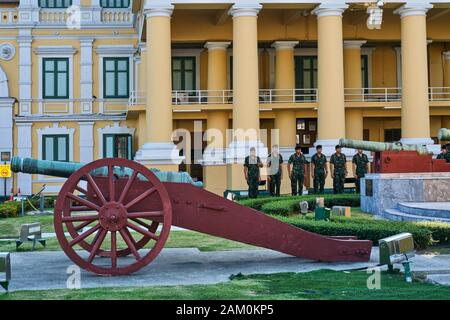 At the Ministry of Defence in Bangkok, Thailand, its grounds decorated with old cannons, soldiers are standing to attention - Stock Photo