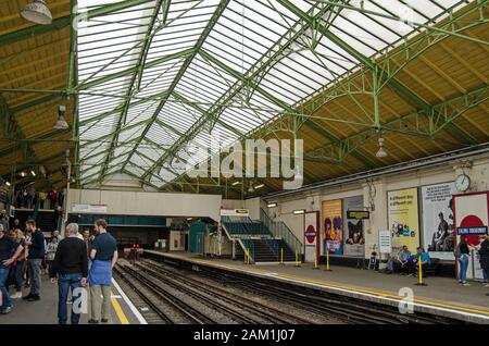 London, UK - June 22, 2019: Passengers on the platform for District Line trains in the historic Edwardian part of Ealing Broadway Station in West Lond - Stock Photo