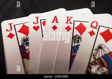 red euchre diamond hand on black background - Stock Photo