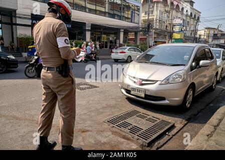 Thailand police officer issuing a traffic ticket, Traffic Cop giving a ticket - Stock Photo