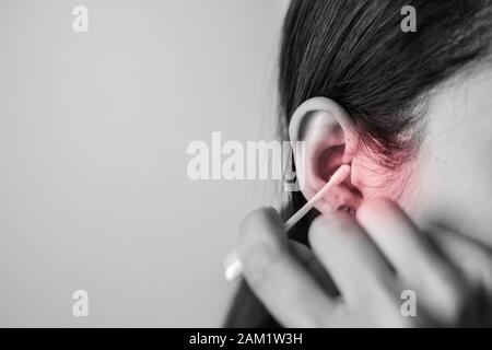 Concept of cleaning in the ear hole. Woman cleaning ear with cotton bud. - Stock Photo
