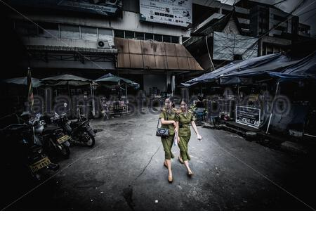 Vientiane, Laos - April 6, 2018: Female soldiers walking outside Talat Sao morning market in Vientiane - Stock Photo