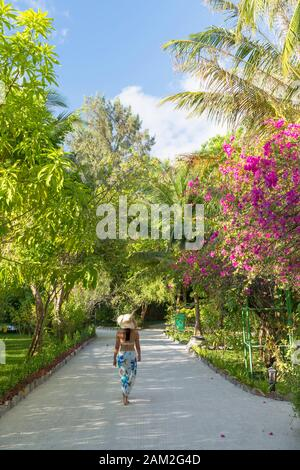 Woman walking in grounds of Olhuveli Beach and Spa Resort, South Male Atoll, Kaafu Atoll, Maldives