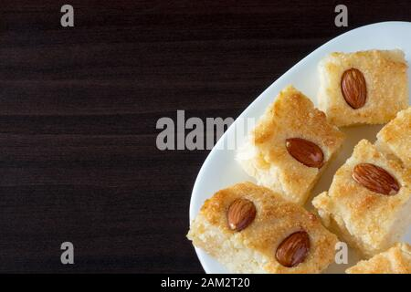 Basbousa (namoora) traditional arabic semolina cake with almond and syrup. Dark background. Copy space - Stock Photo
