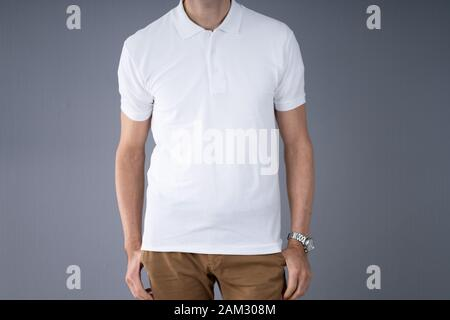 Midsection Of Man In Casuals Standing Against Gray Background - Stock Photo