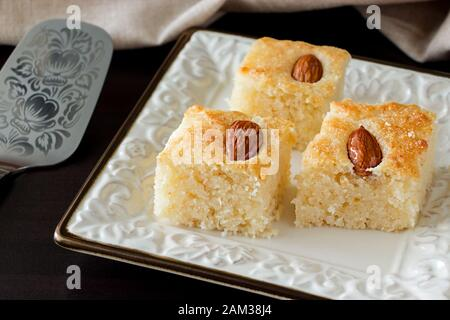 Closeup Three Pieces Basbousa Traditional Arabic Semolina Cake with Almond Nuts Orange Blossom Water. Copy space. Dark background. - Stock Photo