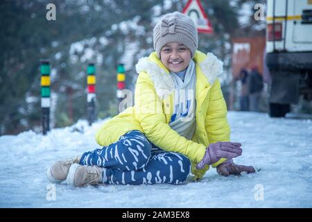 Portrait of an young and cute Indian teenager girl wearing woolen cap and jacket enjoying snowfall and feeling amazed in a snowy evening - Stock Photo