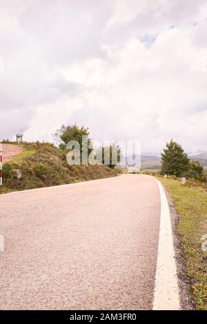 Winding mountain road between green fields and under autumn clouds. Road trip to the most beautiful. travel concept - Stock Photo