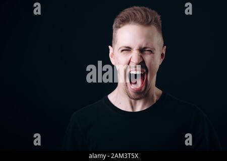 Young Man in Black Screaming With His Eyes Squinted - Stock Photo