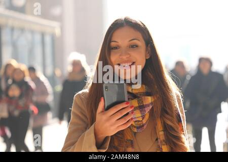 Positive surprised young woman receives good news on her phone while walking in the street with blurred crowd of people on the background