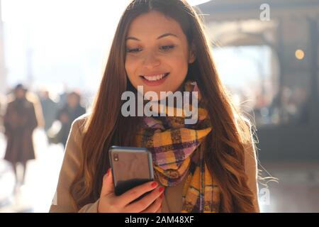 Close up positive young woman receives good news on her phone while walking in the street with blurred crowd of people on the background - Stock Photo