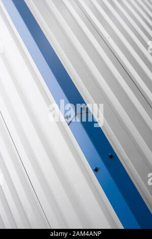 Metal corrugated sheets on a building with a blue metal corners. White aluminium metal corrugated roof or wall sheets on a factories and industrial - Stock Photo